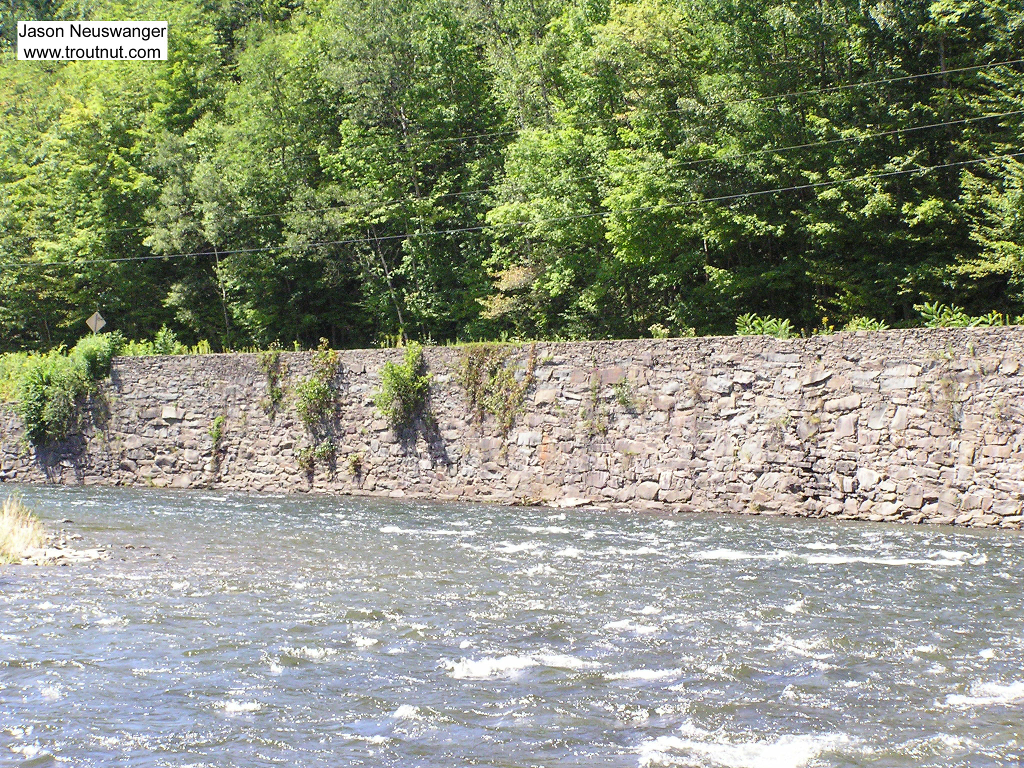 A beautiful deep current tongue runs along a manmade wall on a famous Catskill river. From the Beaverkill River in New York.