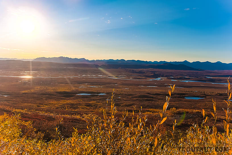 View west across the Maclaren River valley from Maclaren Summit. The Clearwater Mountains make up the highest part of the horizon near the sun. From Denali Highway in Alaska.