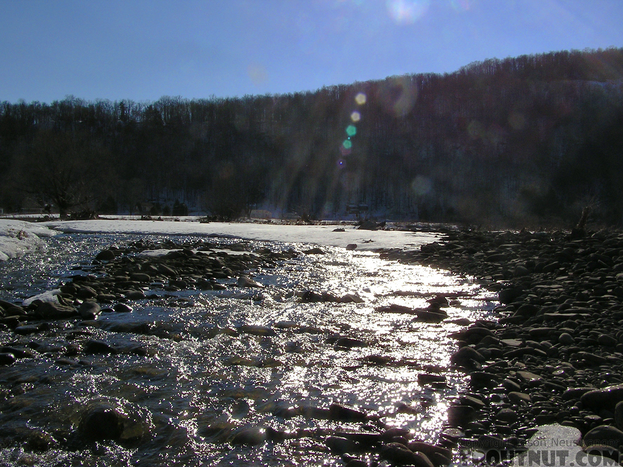 A small tributary tumbles toward a large Catskill river. From the West Branch of the Delaware River in New York.