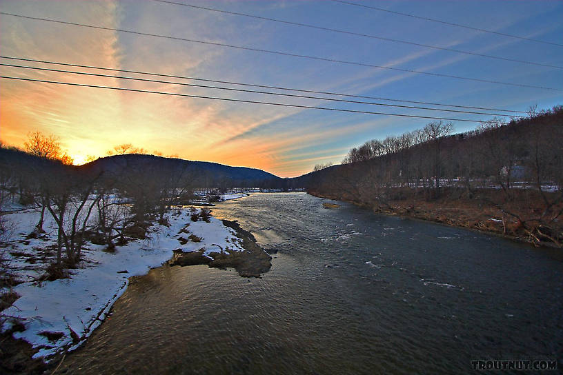 A late winter sunset radiates over a Catskill ridge.  This picture is taken near a popular landing on one of the main tailwaters. From the West Branch of the Delaware River in New York.