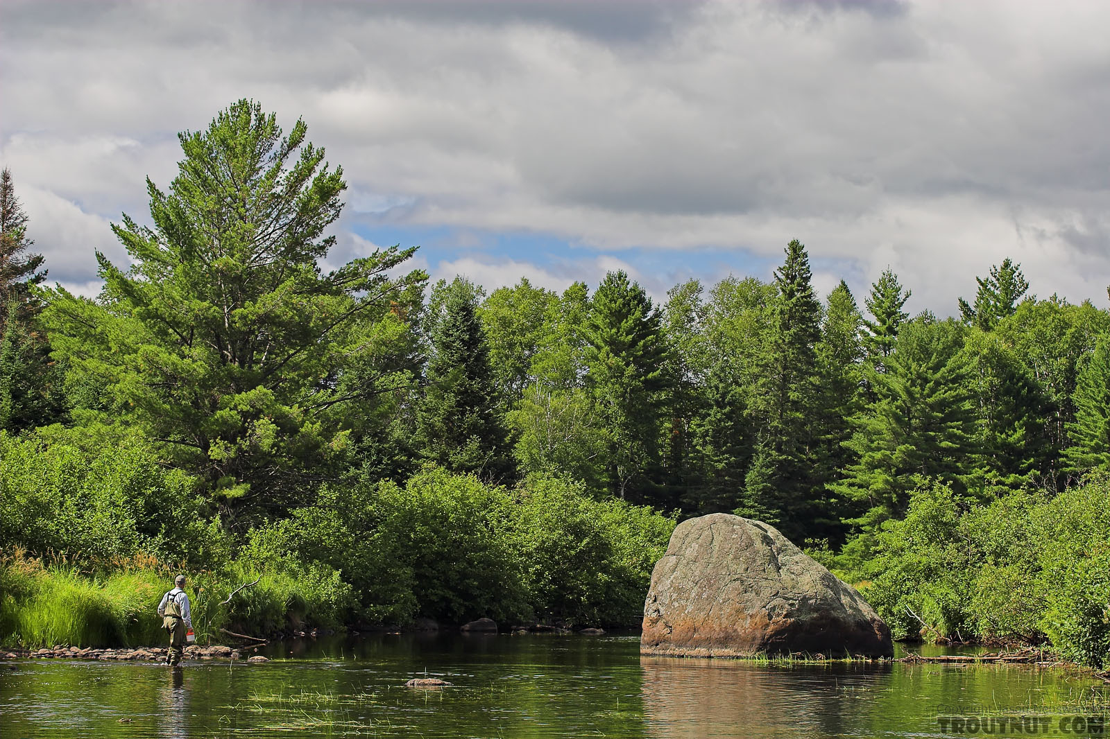 My dad works his way through the shallows of a smallmouth river.  The hole around the large boulder might shelter bass in normal water, but we floated this stretch during a prolonged drought and the fish had left the shallows. From the West Fork of the Chippewa River in Wisconsin.