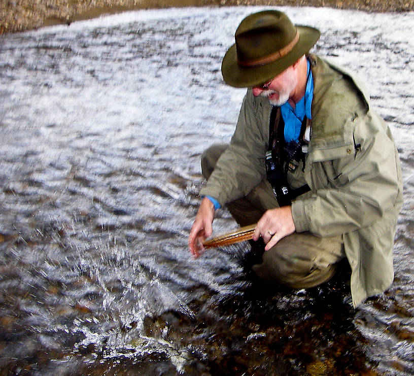 "Another entry into my ""dad dropping a fish"" series.  Here he's dropping his first arctic grayling back in the drink.  It was still on the hook, so we got a better picture shortly. From the Chatanika River in Alaska."