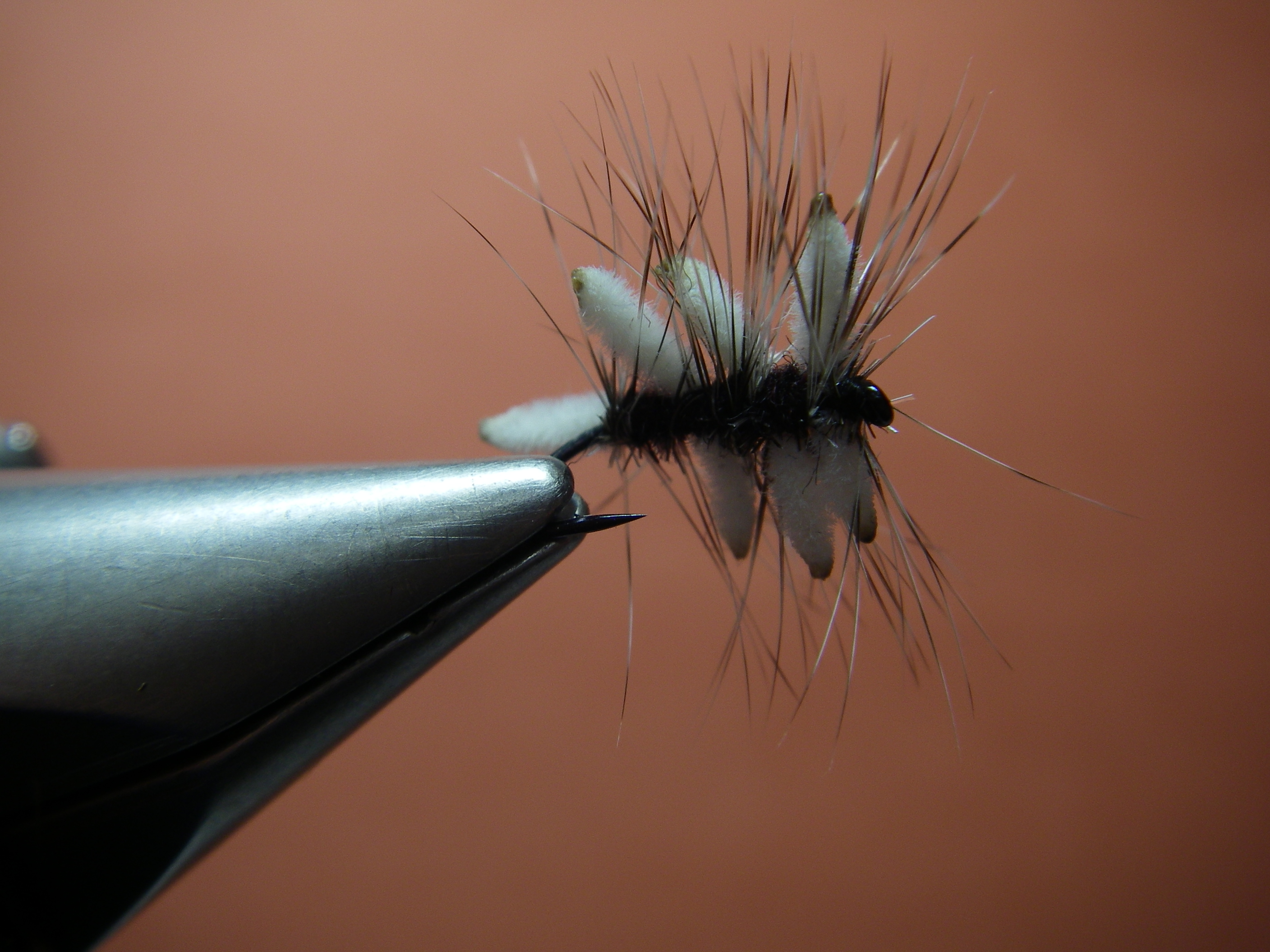 """Traffic-Jam Cluster fly.  Tied on a # 16 standard dry fly hook.  White mini """"Ultra Chenille"""" and size 14 Whiting grizzly hackle."""
