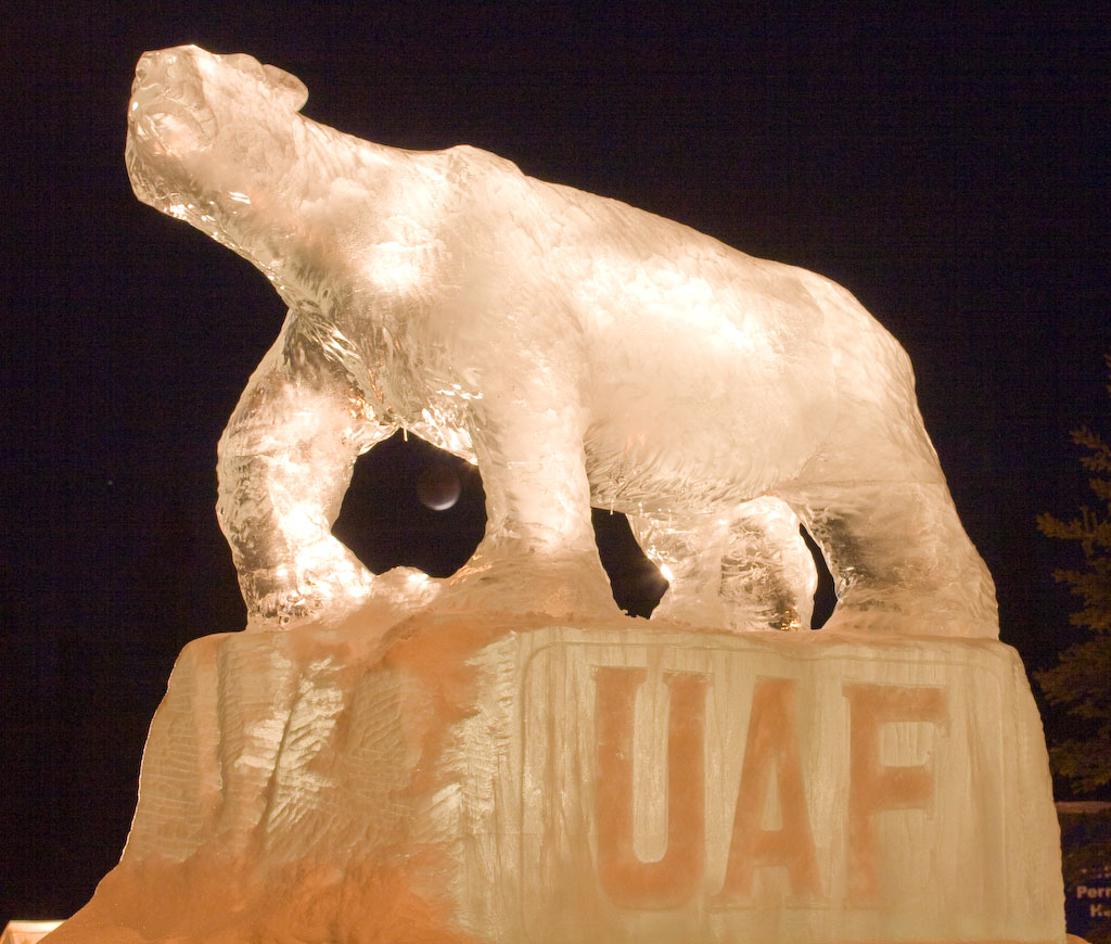Polar bear ice sculpture with the eclipsed moon between its front legs.